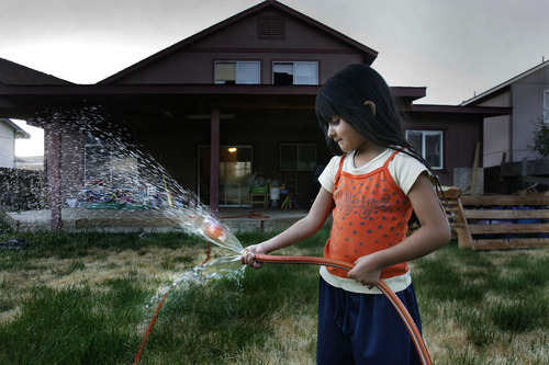Scott Sommerdorf  |  The Salt Lake Tribune              Deisi Gonzalez's daughter Kelsey, 4, plays with the water hose in the backyard of their home in Reno. They will most likely lose the home in a short sale, and move into an apartment. They stopped regularly watering the grass when Deisi stopped making payments.