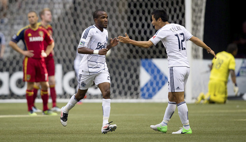 Vancouver Whitecaps' Dane Richards, center, of Jamaica, and Lee Young-Pyo, of South Korea, celebrate Richards' goal against Real Salt Lake during the second half of an MLS soccer game in Vancouver, British Columbia, on Saturday, Aug. 11, 2012. (AP Photo/The Canadian Press, Darryl Dyck)