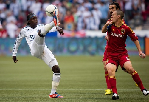Vancouver Whitecaps' Darren Mattocks, left, of Jamaica, corrals the ball with his foot as Real Salt Lake's Will Johnson, right, watches during the first half of an MLS soccer game in Vancouver, British Columbia, on Saturday, Aug. 11, 2012. (AP Photo/The Canadian Press, Darryl Dyck)