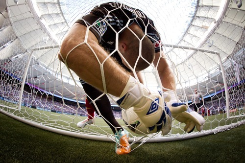 Vancouver Whitecaps goalkeeper Brad Knighton is pushed into the back of the net by Real Salt Lake's Jonny Steele, of Northern Ireland, as he retrieves the ball after Salt Lake's Nat Borchers, not seen, scored a goal during the second half of an MLS soccer game in Vancouver, British Columbia, on Saturday, Aug. 11, 2012. (AP Photo/The Canadian Press, Darryl Dyck)