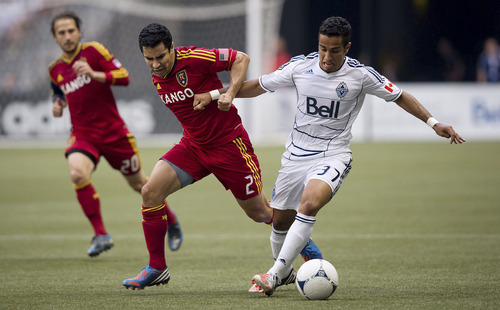 Vancouver Whitecaps' Camilo Sanvezzo, right, of Brazil, fights off Real Salt Lake's Tony Beltran during the first half of an MLS soccer game in Vancouver, British Columbia, on Saturday, Aug. 11, 2012. (AP Photo/The Canadian Press, Darryl Dyck)