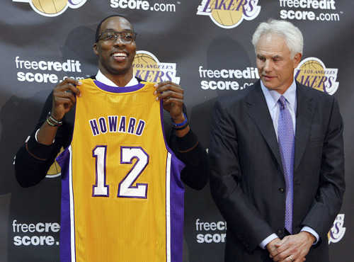 Center Dwight Howard, newly acquired by the Los Angeles Lakers from the Orlando Magic, poses with his Lakers jersey with Lakers general manager Mitch Kupchak, at a news conference at the NBA basketball team's headquarters in El Segundo, Calif. (AP Photo/Reed Saxon)