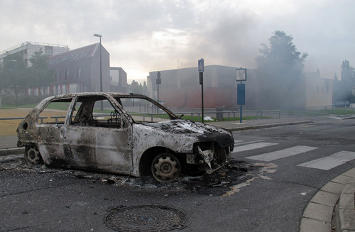 The shell of a burnt out car is seen in a neighborhood of Amiens, France, Tuesday, Aug. 14, 2012. Dozens of young men rioted in a troubled district in northern France after weeks of tensions, pulling drivers from their cars and stealing the vehicles, and burning a school and a youth center. The police department in Amiens says at least 16 officers were hurt by the time the riot ended Tuesday, some by buckshot. (AP Photo/Georges Charrieres)