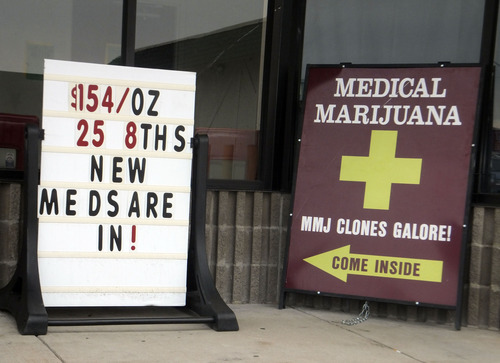 Sidewalk ads outside a west Denver medical marijuana dispensary advertise low prices and ''Clones Galore!'' on Monday, Aug. 13, 2012. After complaints such ads are unseemly, the Denver City Council voted Monday to ban outdoor marijuana advertising including billboards, bus placards and sign-spinners. (AP Photo/Kristen Wyatt)