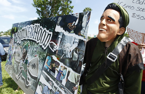 An anti-Romney protester dressed as Romney Hood shows his displeasure with Mitt Romney's economic policies during a Romney campaign stop in Miami, Monday, Aug. 13, 2012.  (AP Photo/J Pat Carter)
