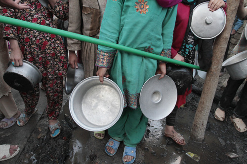Afghans hold their pans as they wait to get free food donated by a private charity during the Muslim holy fasting month of Ramadan at a mosque in Kabul, Afghanistan on Thursday, Aug. 16, 2012. Ramadan is the ninth month of the Muslim year that lasts around 30 days, which strict fasting is observed from sunrise to sunset. (AP Photo/Musadeq Sadeq)