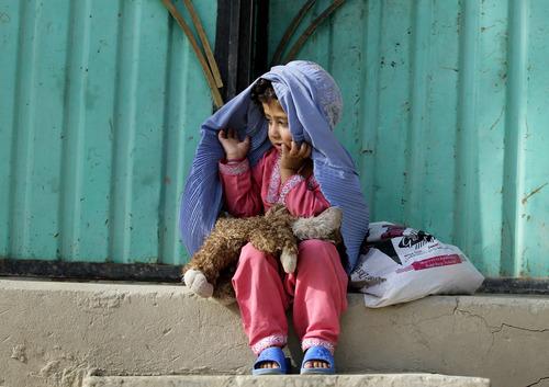 An Afghan girl adjusts her burqa in Kabul, Afghanistan, Thursday, Aug. 16, 2012. (AP Photo/Ahmad Jamshid)