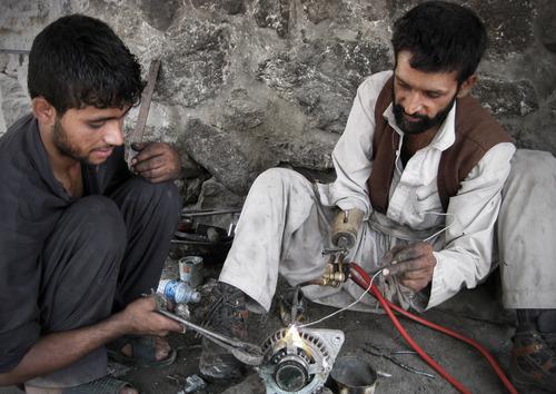 Pashtoon Yar, 35, an Afghan disabled man welds at a metal shop in Jalalabad east of Kabul, Afghanistan, Thursday, Aug. 16, 2012. (AP Photo/Rahmat Gul)