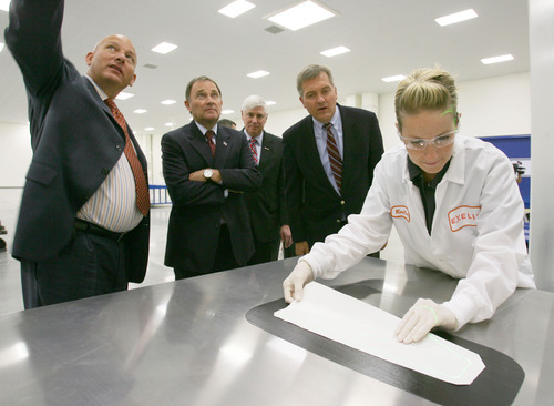 Steve Griffin | The Salt Lake Tribune   Visitors and dignitaries including Utah governor Gary Herbert, center, and US Representative for Utah, Jim Matheson, second from right,  get a guided tour at Exelis, a manufacturing company that makes composite materials for airframes for commercial and military aircraft, during opening of their new composite design and manufacturing center at 5995 west Amelia Earhart Drive in Salt Lake City, Utah Thursday August 16, 2012. Here lab tech lead, Erin Remkes, demonstrates hand lay-up of composite materials.