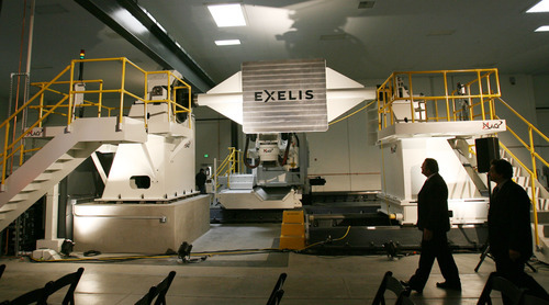 Steve Griffin | The Salt Lake Tribune   Visitors get a close look at an automated fiber placement machine at Exelis, a manufacturing company that makes composite materials for airframes for commercial and military aircraft, during opening of their new composite design and manufacturing center at 5995 west Amelia Earhart Drive in Salt Lake City, Utah Thursday August 16, 2012.