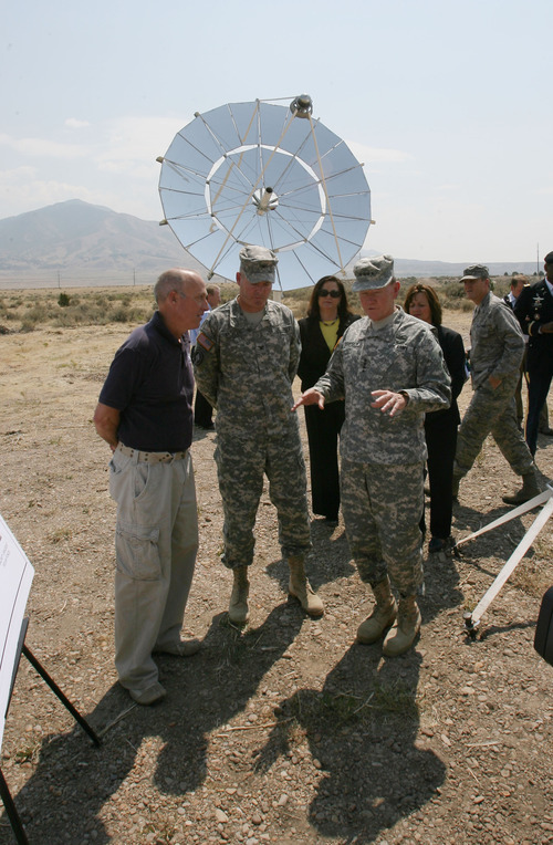 Steve Griffin | The Salt Lake Tribune    General Martin E. Dempsey, chairman of the Joint Chiefs of Staff, right, talks with Colonel Christopher O. Mohan, commander of the Tooele Army Depot, center, and Dallas Hanks, of Utah State University,  following groundbreaking ceremony at Tooele Army Depot, for an array of solar turbines pictured in back.  Infinia Corp., an Ogden company, is making the dish-shaped solar collectors called PowerDishes. The ceremony was at the Tooele Army Depot in Tooele, Utah Friday August 17, 2012.