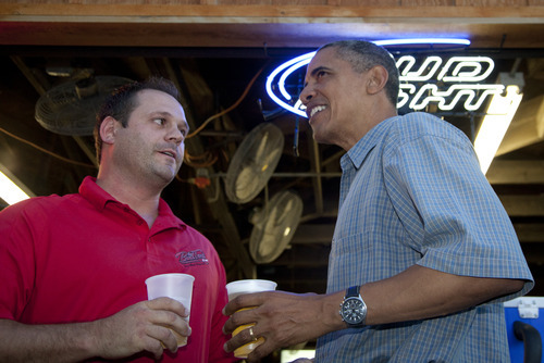 President Barack Obama has a beer with Mike Cunningham II at the beer stand during a visit to the Iowa State Fair, Monday, Aug. 13, 2012, in Des Moines, Iowa,  during a three day campaign bus tour through Iowa. (AP Photo/Carolyn Kaster)