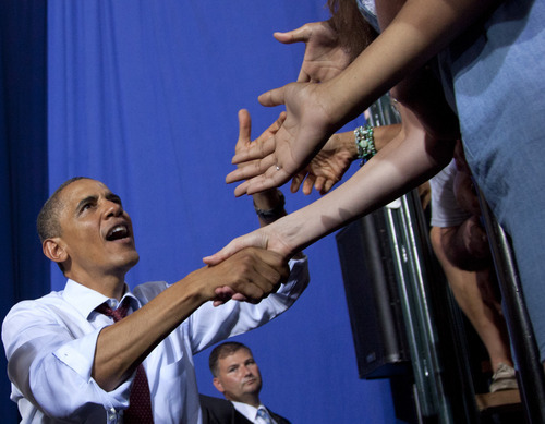 President Barack Obama shakes hands after campaigning Saturday, Aug. 18, 2012, at an event in Windham, N.H., at Windham High School. (AP Photo/Carolyn Kaster)