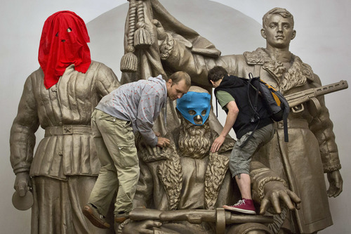 Pussy Riot punk group supporters place masks on a monument to WWII heroes to resemble Pussy Riot members, at an underground station in Moscow on Friday, Aug. 17, 2012.  Three group members who were jailed in March following a guerrilla performance denouncing President Vladimir Putin in Moscow's main cathedral have unwillingly emerged as vivid -- and very different -- characters.  (AP Photo/Yevgeny Feldman, Novaya Gazeta)