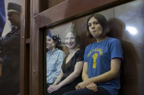 Feminist punk group Pussy Riot members, Nadezhda Tolokonnikova, right, Maria Alekhina, center, and Yekaterina Samutsevich sit in a glass cage at a court room in Moscow, Russia, Friday, Aug. 17, 2012. Security is tight around a Moscow courthouse where three members of the feminist punk band Pussy Riot are to hear the verdict Friday in a trial that could send them to prison for seven years.(AP Photo/Misha Japaridze)