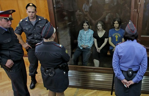 Nadezhda Tolokonnikova, right, Yekaterina Samutsevich, left, and Maria Alekhina, center, members of feminist punk group Pussy Riot seen behind a glass wall at a court in Moscow, Russia, Friday, Aug. 17, 2012. The three members who were jailed in March following a guerrilla performance denouncing President Vladimir Putin in Moscow's main cathedral have unwillingly emerged as vivid — and very different — characters. They await a verdict Friday on charges of hooliganism motivated by religious hatred. (AP Photo/Mikhail Metzel)