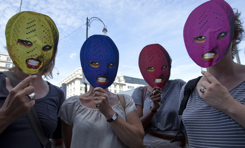 Supporters of the punk band Pussy Riot hold up face masks depicting group members in front of the Russian delegation in Brussels Friday, Aug. 17, 2012. Three group members who were jailed in March, following a guerrilla performance denouncing President Vladimir Putin in Moscow's main cathedral, await a verdict Friday on charges of hooliganism motivated by religious hatred. (AP Photo/Virginia Mayo)
