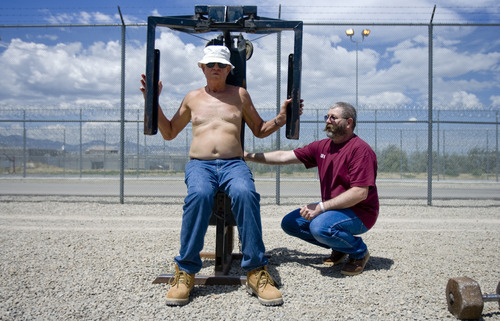 Kim Raff | The Salt Lake Tribune (left) Raymond Fehr, 79, works out in the yard with his ADA assistant Larry Beck in the Lone Peak facility at the Utah State Prison in Draper, Utah on July 26, 2012.  With in Lone Peak the prison has created an ADA unit to provide care for geriatric prisoners, having younger inmates provide support to older inmates.  Beck has been with Fehr for many years and helps Fehr get around which is difficult due to his poor eye sight from macular degeneration.