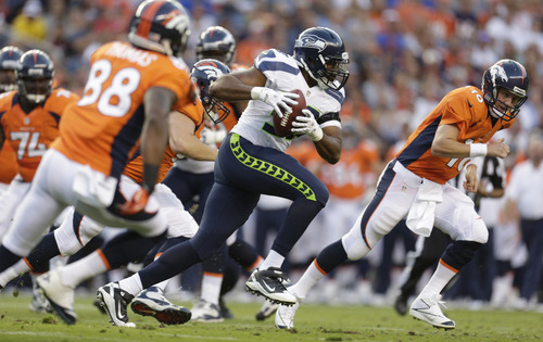 Denver Broncos quarterback Peyton Manning right, looks on as Seattle Seahawks'  K.J. Wright, center, runs with the ball he intercepted from Manning, in the first half of an NFL football preseason game, Saturday, Aug. 18, 2012, in Denver. (AP Photo/Joe Mahoney)