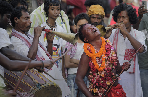 A devotee his face smeared with color and sacrificial blood, dances, during the two-day long Deodhani festival at Kamakhya temple in Gauhati, India, Saturday, Aug.18, 2012. The festival is held to worship the serpent Goddess where goats and pigeons are offered as sacrifice. It is believed that by taking part in this festival, one gets superficial power from goddess Kamakhya. (AP Photo/Anupam Nath)