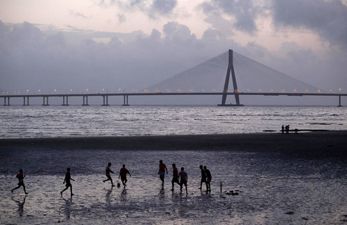 With the Bandra–Worli Sea Link in the background, men play football on the sea shore in Mumbai, India, Saturday, Aug. 18, 2012. (AP Photo/Rajanish Kakade)