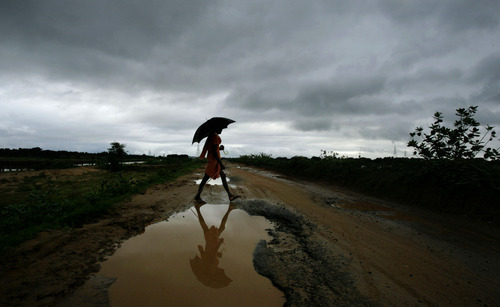 A villager walks with an umbrella as monsoon clouds gather on the outskirts of the eastern Indian city of Bhubaneswar, India, Saturday, Aug. 18, 2012 (AP Photo/Biswaranjan Rout)