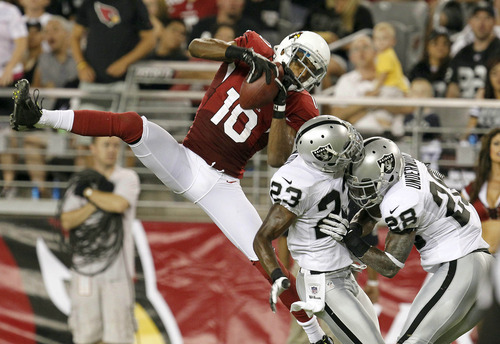 Arizona Cardinals' DeMarco Sampson (10) makes a catch as Oakland Raiders' DeMarcus Van Dyke (23) and Brandon Underwood (28) collide during the second half in a preseason NFL football game Friday, Aug. 17, 2012, in Glendale, Ariz.  The Cardinals defeated the Raiders 31-27.(AP Photo/Ross D. Franklin)