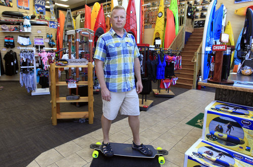 In a photo from Tuesday, Aug. 7, 2012, Andy Schepper, vice president of Summit Sports in Keego Harbor, Mich., stands on a skateboard in his store. With plants shriveling up and outdoorsy types feeling it's too hot to be active in the extreme summer heat, many small business owners with seasonal businesses aren't ringing up a lot of sales. (AP Photo/Carlos Osorio)
