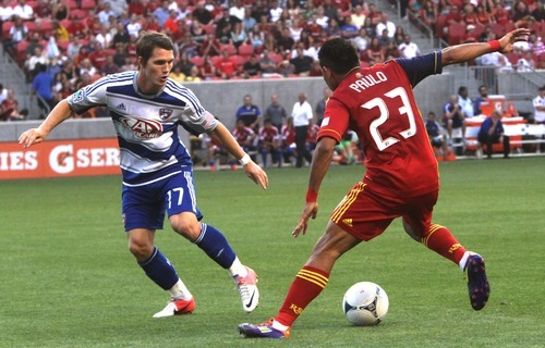 Rick Egan  | The Salt Lake Tribune   Real Salt Lake forward Paulo Jr. (23) tries to get by Zach Lloyd (17)  F.C. Dallas, in MLS soccer action, at Rio Tinto Stadium, Saturday, August 18, 2012.