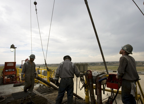 Kim Raff | The Salt Lake Tribune Floorhands work on the on the drilling platform of the 68 Pioneer Rig, a telescoping rig, in Newfield Exploration Company's oil fields in the Central Basin near Roosevelt, Utah on August 9, 2012.