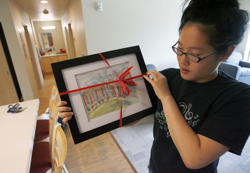 Francisco Kjolseth  |  The Salt Lake Tribune University of Utah sophomore Cindy Chen shows off her prize for being the first to check in to the new Donna Garff Marriott Residential Scholars Hall on Thursday, Aug. 16, 2012. The water color picture of the newly finished residence hall for honors students was an unexpected surprise.