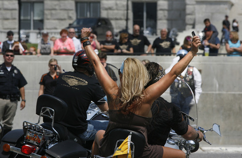 Scott Sommerdorf  |  The Salt Lake Tribune              A rider triumphantly raises her arms as she and others on the ride from Lindon arrive at a ceremony at the state Capitol featuring a special tribute for Agent Jared Francom and Trooper Aaron Beesley, Sunday, August 19, 2012.