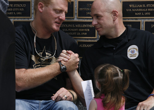 Scott Sommerdorf  |  The Salt Lake Tribune              State Parks Officer Brody Young, left, shakes hands with detective Shane Keyes after Young spoke Sunday at the Law Enforcement Memorial at the Capitol about returning to duty after having been shot nine times while on duty in 2010.
