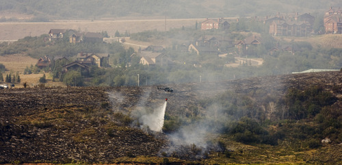 Kim Raff  |  The Salt Lake Tribune Helicopters dump water on a wildfire on the Jordanelle Reservoir near the Jordanelle State Park in Utah on August 19, 2012.