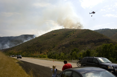 Kim Raff | The Salt Lake Tribune People watch as firefighters battle a new wildfire off Highway 40 outside of Heber in Wasatch County,Utah on August 19, 2012.