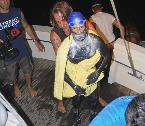In this photo provided by Diana Nyad via the Florida Keys News Bureau, endurance swimmer Diana Nyad is aided after she was pulled out of the water between Cuba and the Florida Keys early Tuesday, Aug. 21, 2012. Nyad has ended her fourth bid to swim from Cuba to Florida after four days of storms, jellyfish stings and shark threats. (AP Photo/Diana Nyad via the Florida Keys News Bureau, Christi Barli)