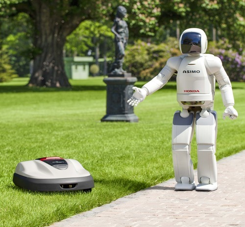 (AP Photo/Honda Motor Co.)  Honda's Asimo walking talking robot shows off the company's  new lawn mower, Milmo, which is operated by robotics technology.