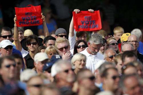 People display signs as Republican vice presidential candidate, Rep. Paul Ryan, R-Wis., speaks during a campaign rally at the American Helicopter Museum & Education Center, Tuesday, Aug. 21, 2012, in  West Chester, Pa. (AP Photo/Matt Rourke)