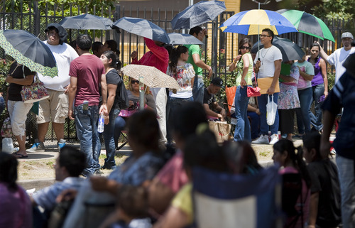 Hundreds of illegal immigrants counting on the DREAM Act passing wait in line to get a passport or any other kind of assistance outside the Mexican Consulate, Tuesday, Aug. 14, 2012, in Houston. Illegal immigrants are scrambling to get passports and other records in order as the Department of Homeland Security starts accepting applications to allow them to avoid deportation and get a work permit. (AP Photo/Houston Chronicle, Nick de la Torre)