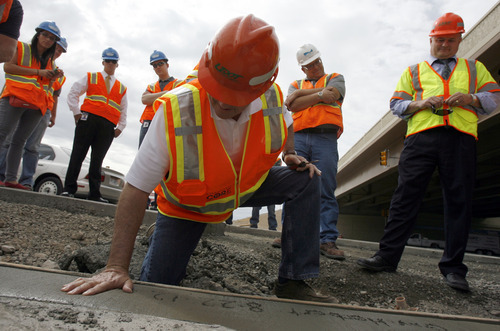 Francisco Kjolseth  |  The Salt Lake Tribune Gov. Gary Herbert makes his mark during a tour of the I-15 CORE project in Orem on Wednesday. The $1.7 billion effort is expected to be finished in time for the holidays.