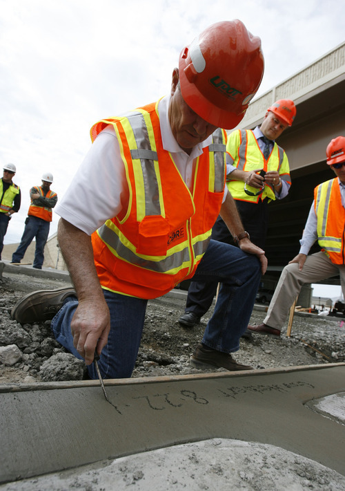 Francisco Kjolseth     The Salt Lake Tribune Gov. Gary Herbert makes his mark during a tour of the I-15 CORE project in Orem on Wednesday. Herbert said the timeliness and savings on the project justify the choice of contractors made by the state.