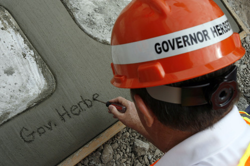 Francisco Kjolseth  |  The Salt Lake Tribune Gov. Gary Herbert makes his mark during a tour of the I-15 CORE project in Orem on Wednesday.