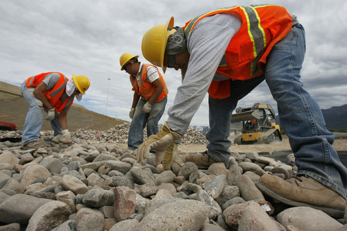 Francisco Kjolseth  |  The Salt Lake Tribune Dan Scott, Joel Frausto and Rafael Velasquez, from left, work on the rock landscaping taking shape along the I-15 CORE project at the Orem Center Street exit on Wednesday. Construction officials now say it is highly probable the work will be finished on the entire project by the holidays.