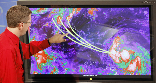 Dr. Rick Knabb, director of the National Hurricane Center, shows some of the possible trajectories tropical storm Isaac could develop in the coming days, Wednesday, Aug. 22, 2012, at the National Hurricane Center in Miami.  (AP Photo/Alan Diaz)