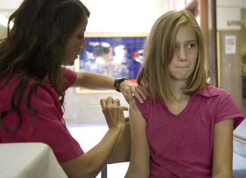Kim Raff  |  The Salt Lake Tribune Daisy Wilson, a registered nurse from Community Nursing Services, administers a vaccination to Serena Mounts during an immunization clinic at Brockbank Junior High School in Magna, Utah on August 15, 2012. The school district holds the clinics to get children caught up on their vaccinations in advance of the school year.