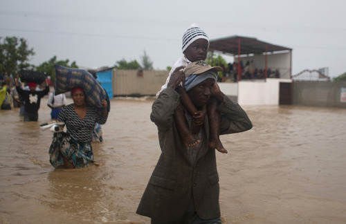 A man carries a child as residents leave an area flooded by Tropical Storm Isaac in Port-au-Prince, Haiti, Saturday, Aug. 25, 2012. Tropical Storm Isaac swept across Haiti's southern peninsula early Saturday, dousing a capital city prone to flooding and adding to the misery of a poor nation still trying to recover from the 2010 earthquake. (AP Photo/Dieu Nalio Chery)
