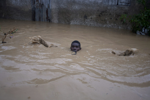 A man carrying a bottle in his mouth slips as he wades through a flooded street, triggered by Tropical Storm Isaac, in Port-au-Prince, Haiti, Saturday, Aug. 25, 2012. Tropical Storm Isaac swept across Haiti's southern peninsula early Saturday, dousing a capital city prone to flooding and adding to the misery of a poor nation still trying to recover from the 2010 earthquake. (AP Photo/Dieu Nalio Chery)