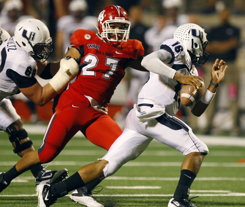 Fresno State's Donavon Lewis, center, pressures Utah State quarterback Chuckie Keeton in the fourth quarter of their NCAA college football game, Saturday, Oct. 15, 2011, in Fresno, Calif. (AP Photo/The Fresno Bee, Eric Paul Zamor)