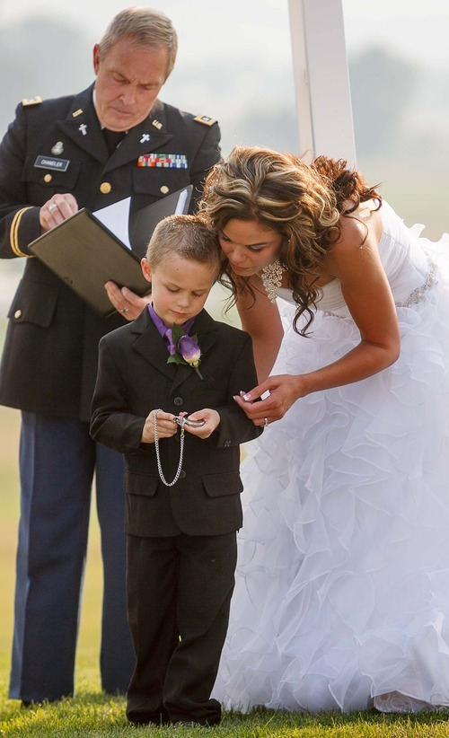 Trent Nelson  |  The Salt Lake Tribune Jen Comer presents her son, T.J. Carver, with a pocket watch as a memento marking Comer's marriage to Daniel Comer in Huntsville, Utah, Aug. 18, 2012. Retired Army Chaplain Charles Chandler performed the ceremony and is at left.