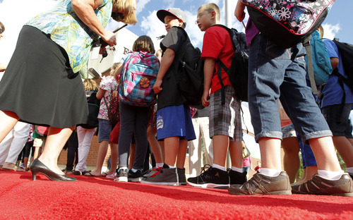 Al Hartmann  |  The Salt Lake Tribune Canyon School District Butler Elementary School students walk down a red carpet to enter the front doors of the school Monday.   They passed by cheering teachers, staff members and the school's Bobcat mascot in a lively welcome back to school.